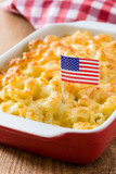 Typical American macaroni and cheese with USA flag on wooden table - 213077260