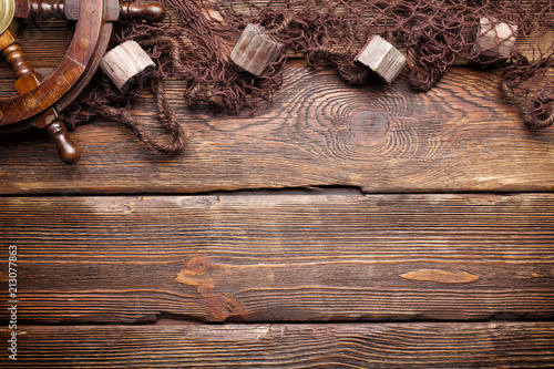 Fishing net and steering wheel on wooden wall background