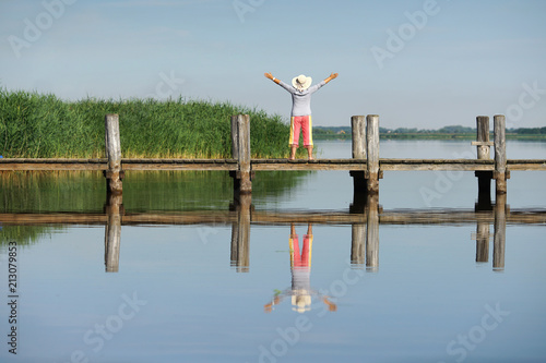Leinwandbild Motiv Seniorin morgens am Steg am See