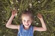 Leinwanddruck Bild - child on green daisy grass in a summer park sunset time