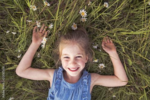 Leinwanddruck Bild child on green daisy grass in a summer park sunset time