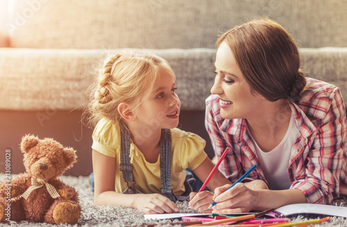 Leinwanddruck Bild Cute Little Girl and Her Beautiful Mother Drawing.