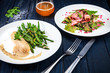 Fried sausage with asparagus on a white plate and salad with ham. Blue wood background, beer, sausage. salt and pepper - 213110670