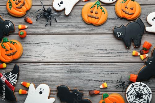 Halloweenowi piernikowi ciastka z cukierkami na drewnianym stole