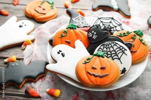 Halloweenowi piernikowi ciastka w talerzu na drewnianym stole