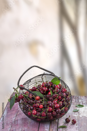 Foto Murales Fresh ripe cherries in an iron basket on a old red board exterior kitchen table