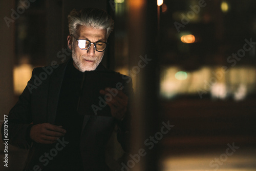 Wall mural Businessman during late working hours in office