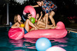 Group of happy friends partying in a swimming pool