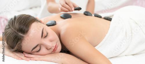 Leinwanddruck Bild Hot stone massage treatment by therapist in spa.