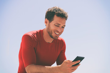 Healthy man watching video on mobile phone after workout training session sitting outside using app on 4g wireless device . Casual young male adult in his late 20s in summer outdoors.