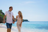 Couple walking on the beach on vacation - 213167412