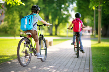 Children with rucksacks riding on bikes in the park near school. Pupils with backpacks outdoors © candy1812