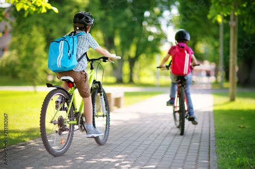 Children with rucksacks riding on bikes in the park near school. Pupils with backpacks outdoors - 213182067
