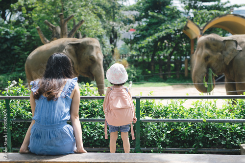 mata magnetyczna Happy mother and daughter watching and feeding elephants in zoo.