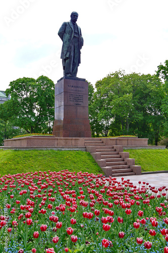 Foto Murales Monument to Taras Shevchenko on the background of a flower bed with beautiful red tulips