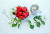 Fruit and herbal tea, beautiful white jasmine flowers and ripe strawberry on the table. Sweet snack.  - 213188426