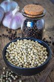 Dried white and black pepper corns with glass bottle on wooden background. - 213189446