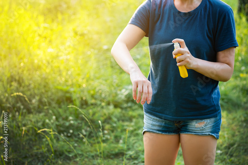 Woman applying insect repellent before forest hike beautiful summer day. - 213191091