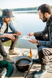 Two fishermen sitting together with fishing tackles sitting during the picnic near the lake - 213192420