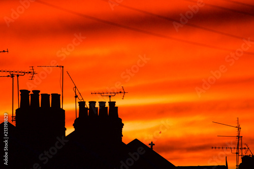 Canvas Baksteen chimneys, tv ariels and telephone lines on terraced houses against orange sunset