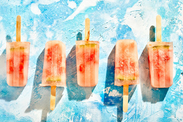 Row of homemade frozen iced melon popsicles