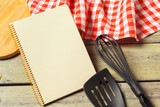 Blank sheet of opened notepad and kitchen utensils on  table with tablecloth, copy space - 213205228