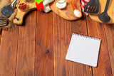 Blank sheet of opened notepad and kitchen utensils on  table with tablecloth, copy space - 213205460