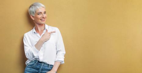 Frau an der Wand zeigt auf leere Fläche