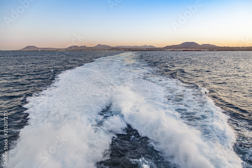 Fotobehang Canarische Eilanden spume of ferry ship with lanzarote skyline in background