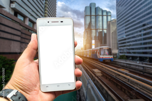 Fototapeta Men use smartphone blurred images in the BTS Skytrain in Bangkok with evening sunset for travel lifestyle transportation concept in the big city.