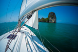 Sailing boat moves under the sails in a tropical sea and aproaches the island - 213218440
