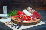 Sliced cured sausage and bresaola with spices and a sprig of rosemary. - 213218695