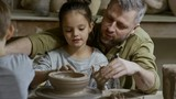Cinemagraph of bearded man and his little daughter forming bowl out of clay spinning on pottery wheel in workshop - 213220446