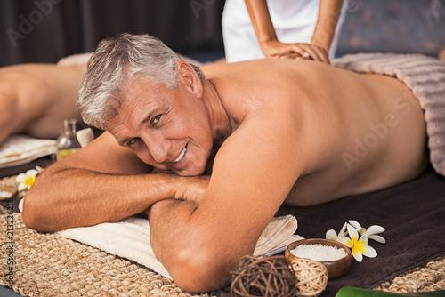 Leinwanddruck Bild Happy mature man getting spa treatment