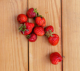 Red strawberries lying on a wooden table.