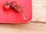 Cherry tomatoes on a branch on a red plate. - 213227803