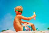 sun protection- happy little boy with suncream at beach
