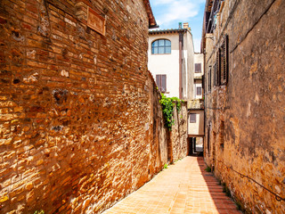 Picturesque medieval narrow street of San Gimignano old town, Tuscany, Italy.