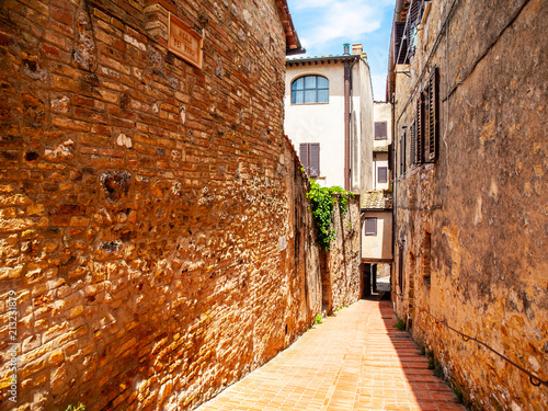 Picturesque medieval narrow street of San Gimignano old town, Tuscany, Italy. - 213231879