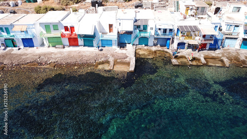 Foto Murales Aerial drone bird's eye view photo of picturesque and colourful fishing village of Klima with traditional character and uphill village of Plaka at the background, Milos island, Cyclades, Greece