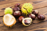 Heap of green prickly and brown smooth chestnuts on old wooden rustic brown table - 213237243