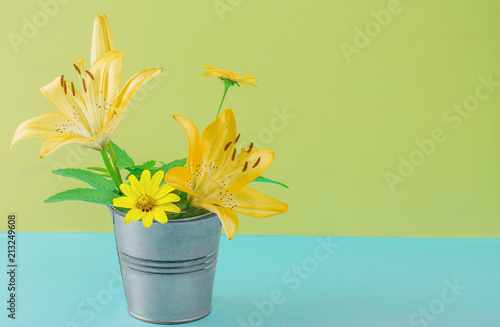 Foto Murales yellow bouquet of flowers in a bucket on a colored background for designers