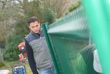 Man looking down garden fence - 213251899