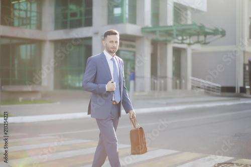 Foto Murales elegant businessman in blue suit walking out of bank