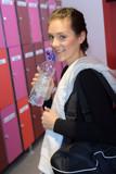Woman in locker room with bottle of water - 213254637