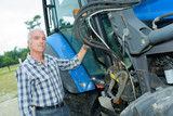 Farmer stood next to tractor - 213255434