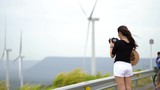 Asian women tourists are taking a picture of a wind turbine at a scenic spot. - 213258446