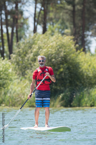 man enjoying a ride on the lake with paddleboard - 213270271