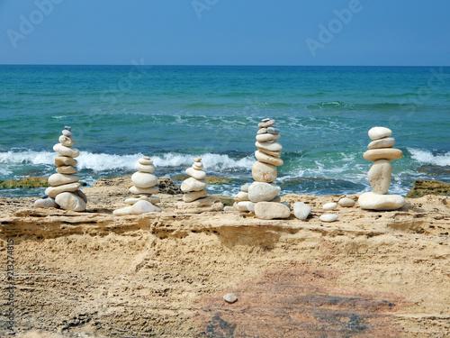 Plexiglas Zen Stenen Figures on the sea coast, built of stones by people.