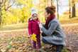 family, season and people concept - happy mother and little daughter with autumn leaves at park